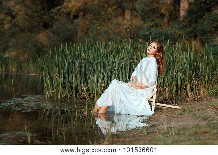 Girl White Dress Sitting Dipping Feet In The Lake.