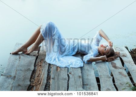 Gentle Girl In White Dress Lying On A Wooden Pier.