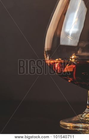 Snifter Of Brandy In Elegant Typical Cognac Glass On Dark Background