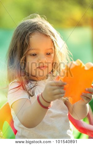 Little girl with toy in hands. Portrait in nature with warm sunlight.Shallow depth of field. Selective focus.