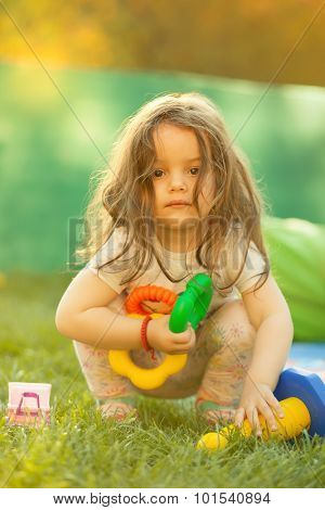 Little girl with toys in hands. Portrait in nature with warm sunlight.