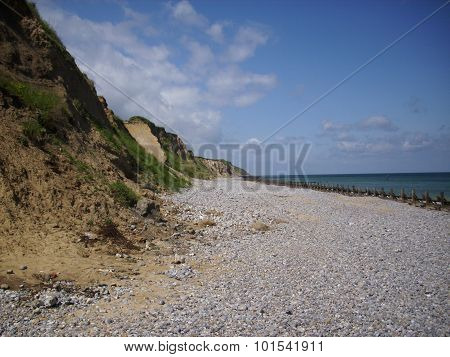 Shingle and sand beach with calm sea, breakwaters and cliffs