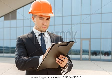 Handsome architect taking notes
