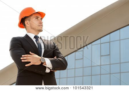 Architect standing on site with his arms folded