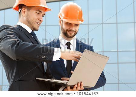 Pair of engineers examining their plans on laptop