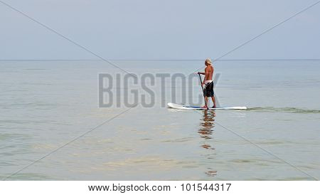 Man On The Paddle Board Sailing Along The Beach