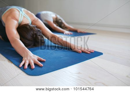 Two Women Relaxing In Child Pose Doing Yoga