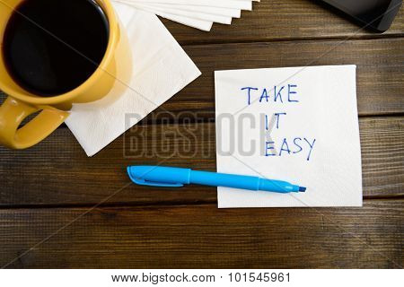 Take it easy -  handwriting on a napkin with a cup of coffee