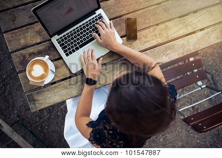 Woman Working On Her Laptop At Outdoor Cafe