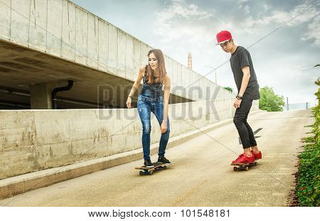 Skateboarder woman and man rolling down the