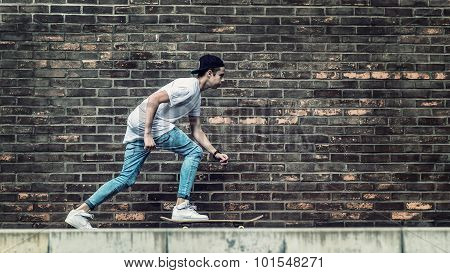 Skateboarder boys by brick wall