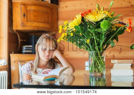 Portrait of 7-8 years old kid girl reading a book at the table at home