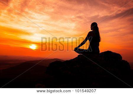 Yoga practicioner sitting on rock during the sunset meditation