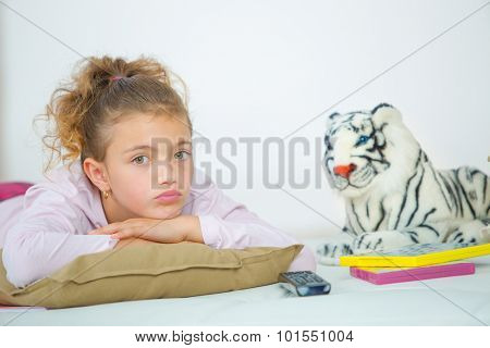 Little girl sat next to stuffed toy