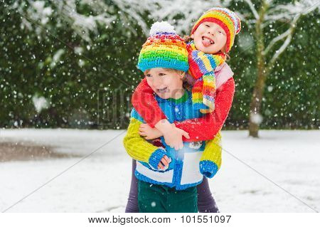 Kids in colorful clothes playing in the park under snowfall, wearing colorful knitwear