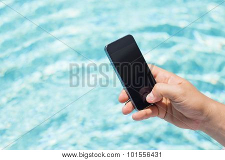 Mobile phone in hand by the pool