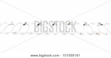 Line border made of multiple safety pins isolated on white background