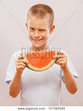 Funny and happy little boy eating watermelon.