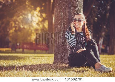 girl is talking on the phone under the tree