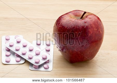 Pink pills blister pack and fresh red apple
