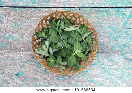 Mint Leaves In Wicket Basket On Wooden Background