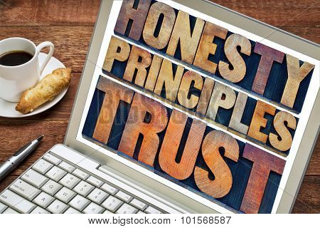 honesty, principles and trust concept - words in vintage letterpress wood type printing blocks stained by color inks on a laptop screen with a cup of coffee