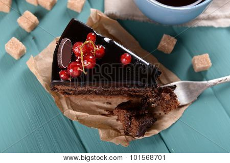 Tasty chocolate cake with berries and cup of tea on table close up