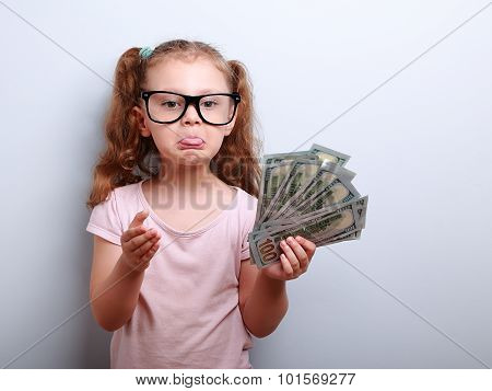 Fun Grimacing Kid Girl Explaining And Showing Tongue Holding Money In Hand
