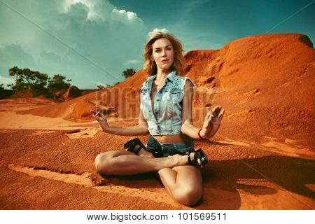 Beautiful woman sitting in lotus on a peak over the mountains
