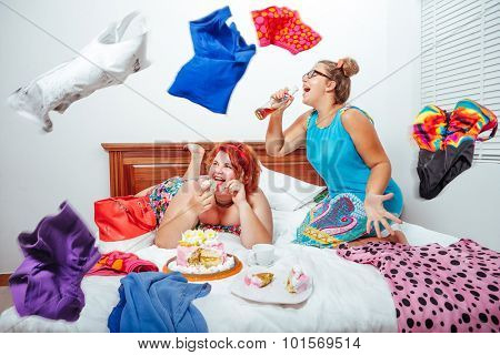 Portrait of beautiful plus size curly red hair young woman eating sweet pastry in bed