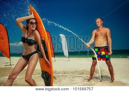 Portrait of young couple having fun with hose splashing summer rain on beach