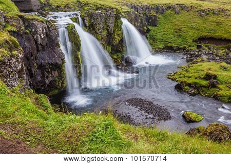 Cascade deep falls Kirkyyufell Foss on the grassy mountains. Iceland - the country of mountains, the rivers and falls