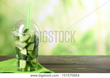 Ingredients for healthy drink in plastic cup, on wooden table, on bright background