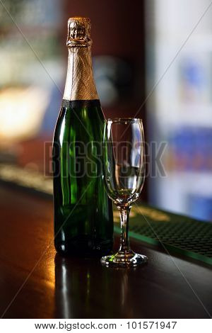 Glass of champagne, on bar counter, on blurred lights background