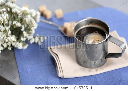Metal cup of flavored coffee with lump sugar and flowers on table with napkin, closeup