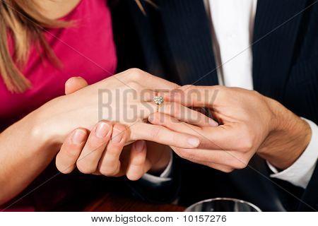 Man sticks ring on finger of fiance