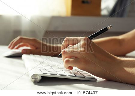 Female hand with pen typing on keyboard at table, closeup