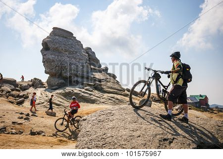 Unidentified group of bikers climbs the hill in Bucegi Mountains
