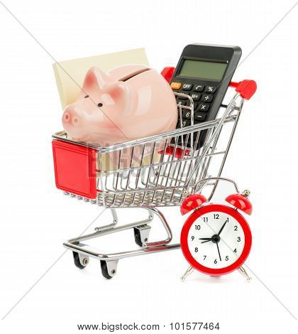 Piggy bank, paper and calculator in shopping cart