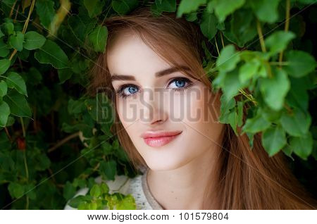 Happy Smiling Beautiful Young Woman Surrounded By Green Leaves
