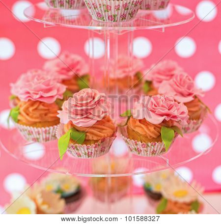 Delicious cupcakes with cream roses on the glass plate