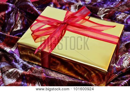 Golden Gift Box With Red Bow Over Colorful Velvet