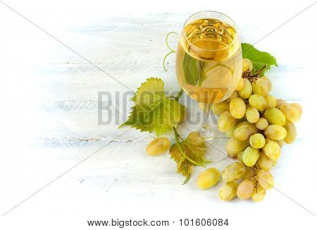 Glass white wine with grapes and leaf on wooden board