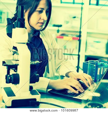 laboratory assistant analyzes of DNA sequence on the computer. Colored photo
