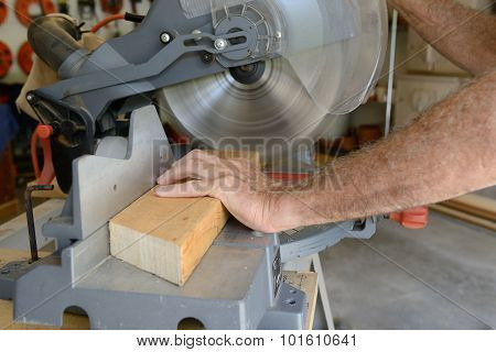 Builder Using Saw to Cut Wood in Shop