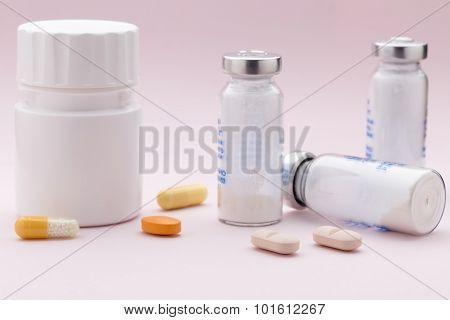 The set of medicine bottles, colorful pills and injection syringe