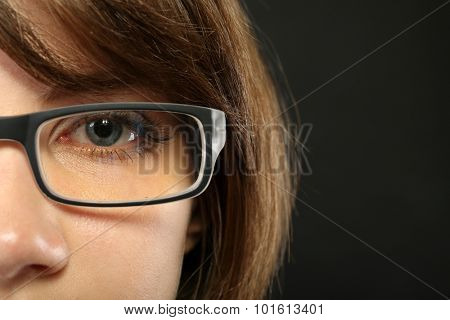 Attractive young woman with glasses on gray background