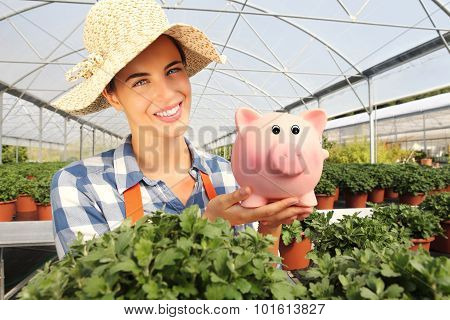 Smiling Woman In Greenhouse, With Piggy Bank,