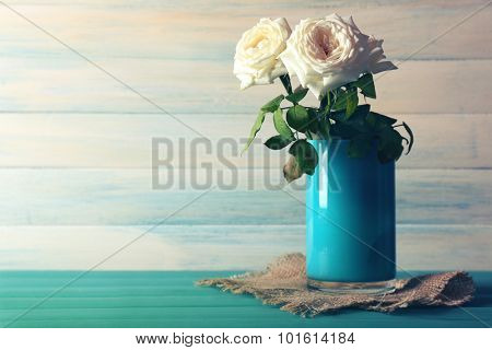 Beautiful white roses in glass vase with sackcloth on wooden background