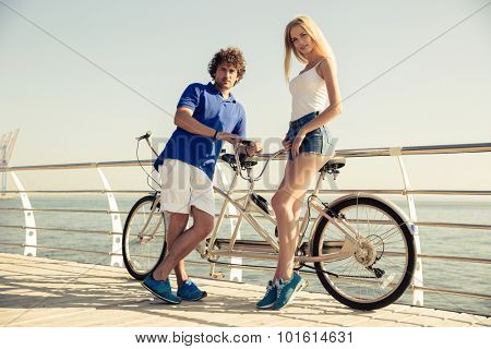 Portrait of a happy couple standing near tandem bicycle outdoors